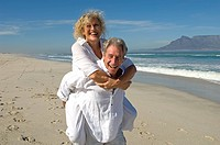 Portrait of senior couple having piggyback ride on beach, Table Mountain in background, Table View, Cape Town, Western Cape Province, South Africa