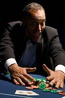 Ecstatic man gathering winning chips at casino table