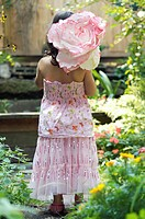 A Rear View of a young girl dressed up standing in a garden and carrying a paper flower