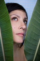 A woman behind banana leaves