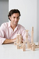 A man using wooden building blocks at a desk