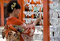 A woman tying a prayer to a string in a temple in Japan