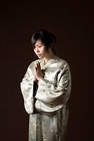 a woman in a kimono bowing