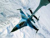 An F-16 Fighting Falcon showing the aggressor paint scheme disconnects from a KC-10 Extender after being refueled during a Red Flag-Alaska exercise Ap...
