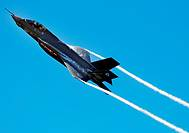 An F-35 Lightning II Joint Strike Fighter test aircraft banks over the flightline at Eglin Air Force Base, Fla , April 23, sending contrails streaming...