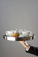 A waiter holding a tray with coffee cupy and muffin