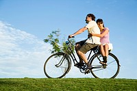 A man riding a bicycle and a young woman sitting on the back