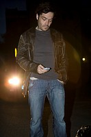 A man standing in front of headlights looking at his mobile phone