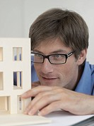An architect examining an architectural model