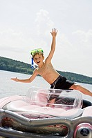 A young boy standing in an inflatable raft on a lake