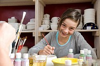 A young girl painting in a pottery studio