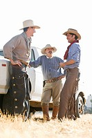 Three cowboys standing in a field next to a truck