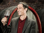 A vintner holding a glass of red wine and smiling