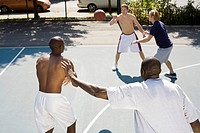Four men playing basketball