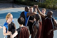 Two teams of basketball players shaking hands