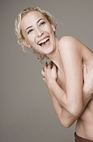 A semi_dressed woman laughing in surprise, portrait