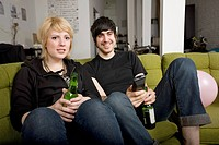 A young couple sitting on a sofa with a remote control and bottles of beer