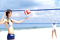Young women playing volleyball on the beach