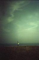 Person by the sea under dramatic sky.