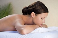 Young woman lying on massage table with eyes closed