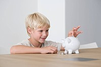 Little boy putting coin into piggybank