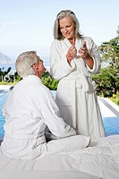 Middle aged couple in bathrobes by the pool