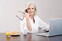 Woman using laptop and eating breakfast