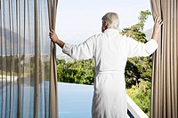 Middle aged man wearing bathrobe pulling back curtains in front of swimming pool
