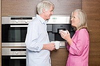 Middle aged couple standing in kitchen with cups of coffee