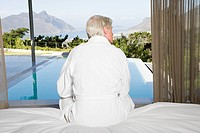 Rear view of middle aged man sitting on bed with view out to swimming pool