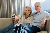Middle aged couple sitting on couch together watching TV
