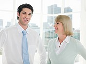 Smiling Businessman and Businesswoman standing in office