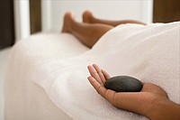 Woman on massage table holding stone