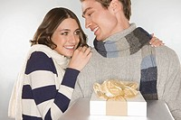 Happy young couple holding a gift