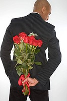 Man with a bunch of roses behind his back