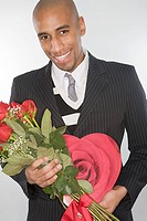 Smiling man holding a bunch of roses