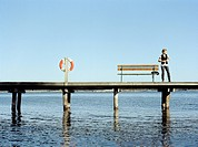 A young woman on a jetty Sweden.