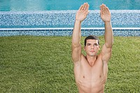 Man stretching by swimming pool