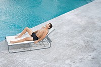 Man on lounge chair by pool