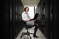 Female computer technician working on a server