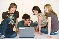 Four young people chill at the laptop
