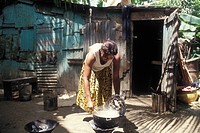 Los Minas, Dominican Republic, A woman cooking over an open fire outside her house