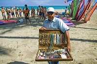 Cabarete,Dominican Republic,West Indies,Caribbean,Man selling beaded necklaces on the beach,with a windsurfing lesson taking place in the background