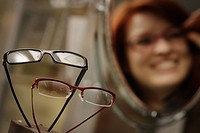 Optician´s window display with woman trying on glasses in mirror in background