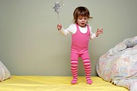 Young girl, two and half years old, bouncing on her bed with a fairy wand