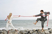 Young businesswoman and businessman pulling red rope on beach