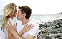 Young affectionate couple about to kiss on beach