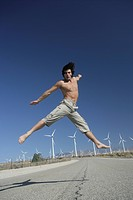 Shirtless young man leaping in midair on empty road.