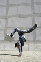 Young acrobatic businessman doing handstand and balancing briefcase