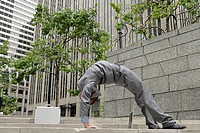 Portrait of flexible businessman doing backbend on steps in city